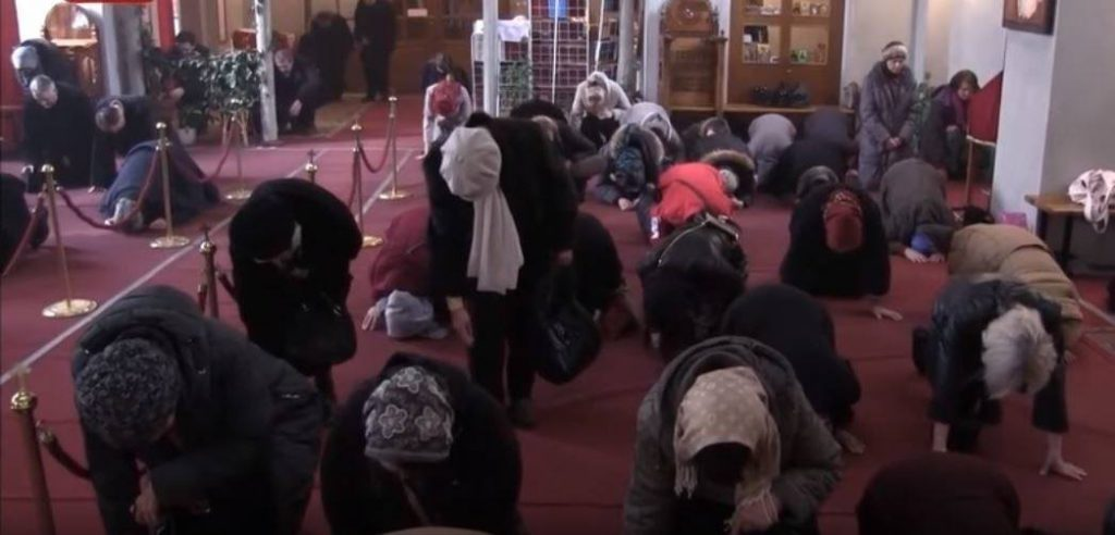 Orthodox faithful standing and prostrating in church