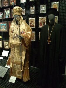 Gold liturgical vestments for an Orthodox bishop (left) and non-liturgical black cassock with cross pendant (right).