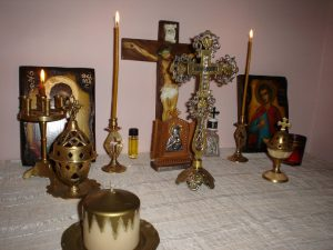 An Orthodox home altar with icons, a cross, and an incense burner.