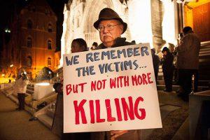 Man holding sign against capital punishment.