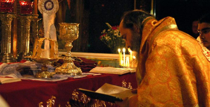 Orthodox Priest prepares the Sacrament of Holy Communion in a Church